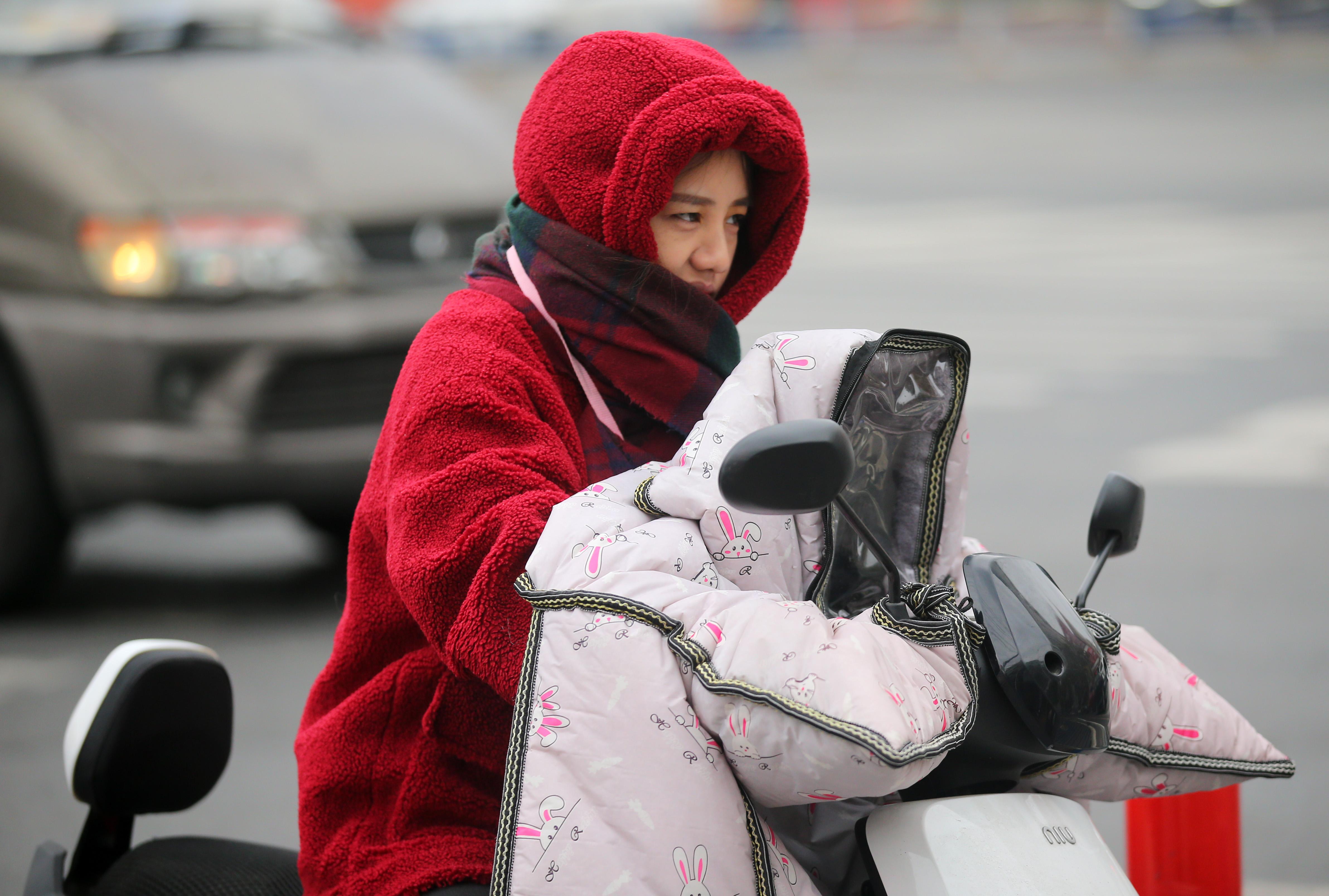 """随着一股较强冷空气东移南下,今晨,全省各地的气温都在10℃以下,相较昨天有了大幅的下降。南通今天最高气温只有9℃,早晨,不少市民出行时纷纷""""全副武装""""抵御严寒。"""
