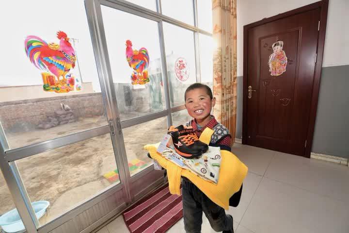 ↑在青海海东市互助县五十镇班彦新村,刚刚迁入新居的儿童手捧新买的衣服。班彦新村129户村民原来居住在海拔2800米的山上。脱贫攻坚精准识别时,这个村贫困发生率高达57%。2016年,受益于易地扶贫搬迁政策,村民们整体搬迁到山下统一规划、统一建设的新村。新村水、电、天然气等一应俱全;农家乐、扶贫车间等政策的落实,也让移民们的生活有了保障(2017年1月27日摄)。